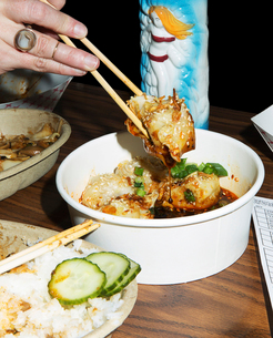 Copped hand holding food with chopsticks at table in restaurantの写真素材 [FYI03729412]