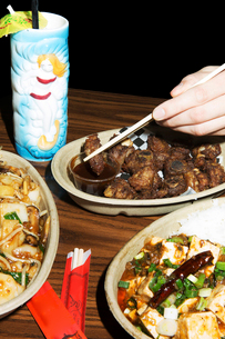 Copped hand holding chopsticks with food over dip at table in restaurantの写真素材 [FYI03729416]