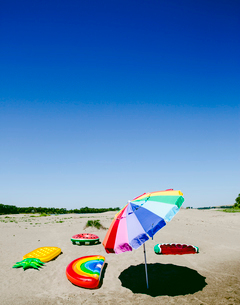 Parasol and inflatable rafts at beach against clear sky during sunny dayの写真素材 [FYI03729875]