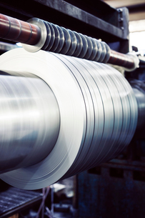 Close-up of metallic sheets spinning on machine at industryの写真素材 [FYI03730410]