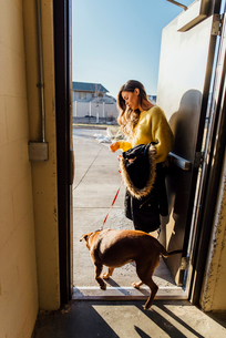 Side view of woman with dog standing at doorwayの写真素材 [FYI03730626]