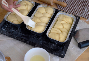 Cropped hand of baker applying egg white with brush on bread in containerの写真素材 [FYI03730678]