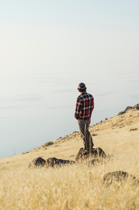 Side view of man looking at sea while standing on rock against skyの写真素材 [FYI03731059]