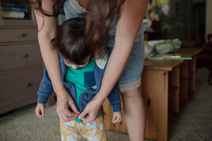 Midsection of mother dressing daughter while standing at homeの写真素材 [FYI03731466]