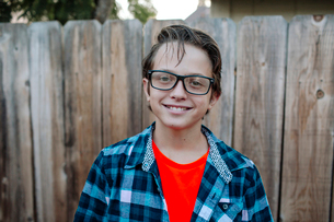 Portrait of smiling boy standing against wooden fence at yardの写真素材 [FYI03731618]