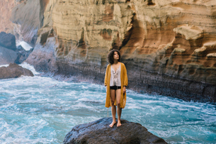 Woman looking up while standing on rock at Reunion islandの写真素材 [FYI03731917]