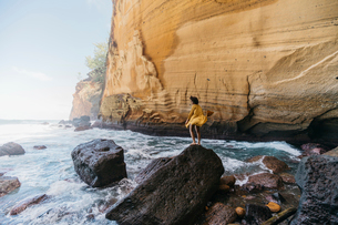 Side view of woman standing on rock at Reunion islandの写真素材 [FYI03731924]