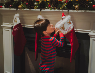 Side view of curious boy looking at toy in sock hanging by fireplace during Christmasの写真素材 [FYI03732275]