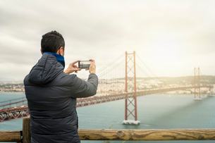 Rear view of man in warm clothing photographing April 25th Bridge against cloudy skyの写真素材 [FYI03732496]