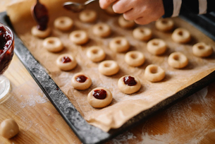 Cropped hand of woman preparing sweet food in baking sheet on wooden table at homeの写真素材 [FYI03732551]