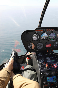 Low section of man relaxing in cockpit of helicopterの写真素材 [FYI03732824]