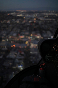 Illuminated cityscape seen through helicopter's windshield at nightの写真素材 [FYI03732827]