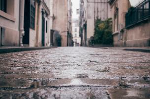 Wet empty alley amidst buildings in city during rainy seasonの写真素材 [FYI03733243]