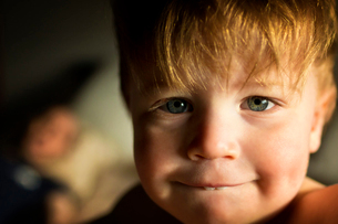 Close-up portrait of cute boy biting lip at homeの写真素材 [FYI03733290]