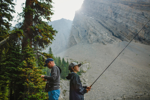 Side view of father and son fishing against mountains at forestの写真素材 [FYI03733600]