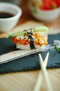 Close-up of sushi served by chopsticks on table at restaurantの写真素材 [FYI03733700]