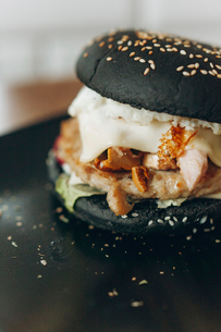 Close-up of black bun burger in plateの写真素材 [FYI03733703]