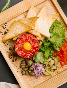 Close-up of steak tartare with toasted bread and vegetables in wooden trayの写真素材 [FYI03733811]
