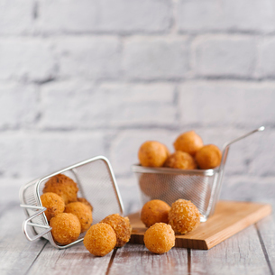 Close-up of fried snacks in metallic baskets on wooden tableの写真素材 [FYI03733817]