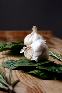 Garlic bulbs with spinach on wooden table against black backgroundの写真素材 [FYI03733831]
