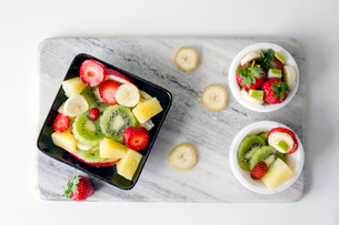 Overhead view of fruit salad on marble cutting board over white backgroundの写真素材 [FYI03733855]