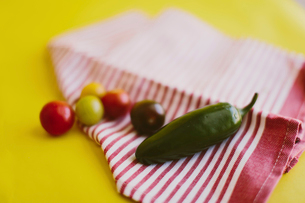 Close-up of jalapeno pepper and cherry tomatoes on textile over yellow backgroundの写真素材 [FYI03733886]