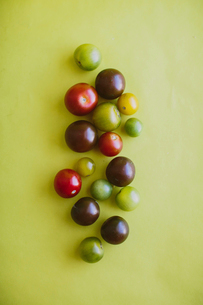 Overhead view of fresh heirloom cherry tomatoes over yellow backgroundの写真素材 [FYI03733891]