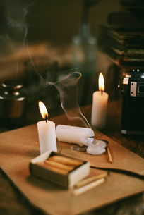 High angle view of burning candles with matchbox and envelop on tableの写真素材 [FYI03734179]