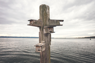 Birdhouse on wooden post by lake against cloudy skyの写真素材 [FYI03734288]