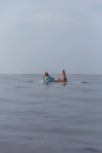 Side view of carefree woman lying on surfboard in sea against skyの写真素材 [FYI03734451]