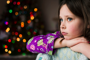 Thoughtful girl against illuminated Christmas Tree at homeの写真素材 [FYI03734592]