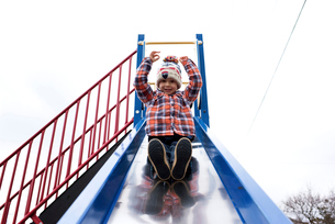 Low angle portrait of smiling boy sliding against clear sky at parkの写真素材 [FYI03734853]