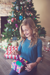 Girl holding Christmas present while sitting on floor at homeの写真素材 [FYI03735054]