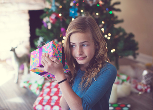 Girl holding Christmas present while sitting at homeの写真素材 [FYI03735055]