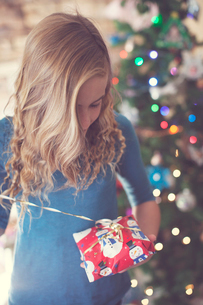 Girl opening Christmas present while standing at homeの写真素材 [FYI03735057]