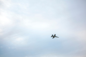 Low angle view of fighter plane against cloudy skyの写真素材 [FYI03735060]