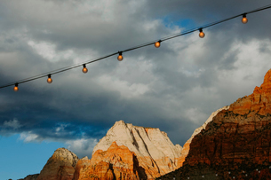 Low angle view of illuminated light bulbs against mountains and cloudy sky at Zion National Parkの写真素材 [FYI03735125]