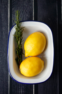 Overhead view of lemons with rosemary in bowl on wooden tableの写真素材 [FYI03735174]