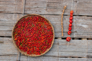High angle view of red chili peppers in wicker basket by tomatoes on wooden floorの写真素材 [FYI03735656]