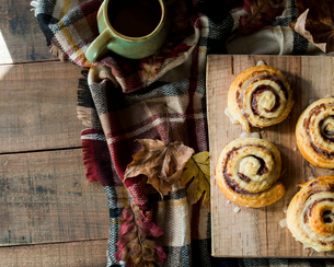 Overhead view of cinnamon rolls by autumn leaves with coffee and blanket on wooden tableの写真素材 [FYI03735699]