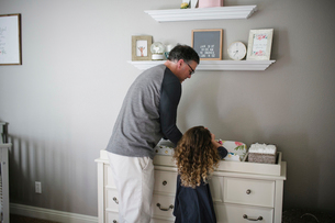 Father and daughter picking baby girl lying on cabinet at homeの写真素材 [FYI03736310]