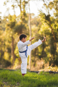 Side view of boy practicing karate on grassy field at parkの写真素材 [FYI03736413]