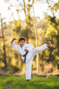 Full length of boy practicing karate on grassy field at parkの写真素材 [FYI03736416]