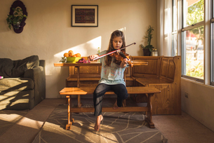 Girl playing violin while sitting on wooden seat at homeの写真素材 [FYI03736468]