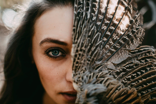 Close-up portrait of confident young woman with feathersの写真素材 [FYI03736589]