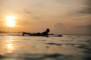 Side view of silhouette man surfing on sea against sky during sunsetの写真素材 [FYI03736637]