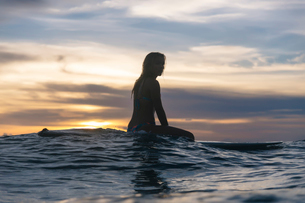 Side view of young woman sitting on surfboard in sea against cloudy sky during sunsetの写真素材 [FYI03736671]