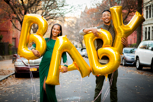 Portrait of happy expectant couple holding helium baby text balloons while standing on road in cityの写真素材 [FYI03736708]
