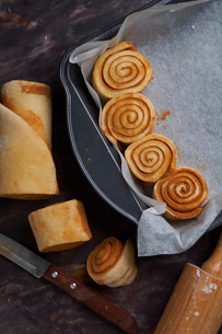 Close-up of rolled up cinnamon bun's dough in baking sheet on kitchen islandの写真素材 [FYI03736737]