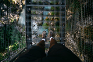 Low section of hiker on metallic footbridge over stream at forestの写真素材 [FYI03737033]